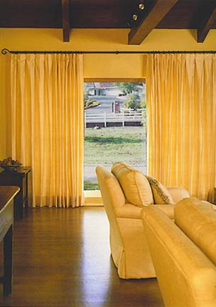 Yellow cotton drapes on iron rod
